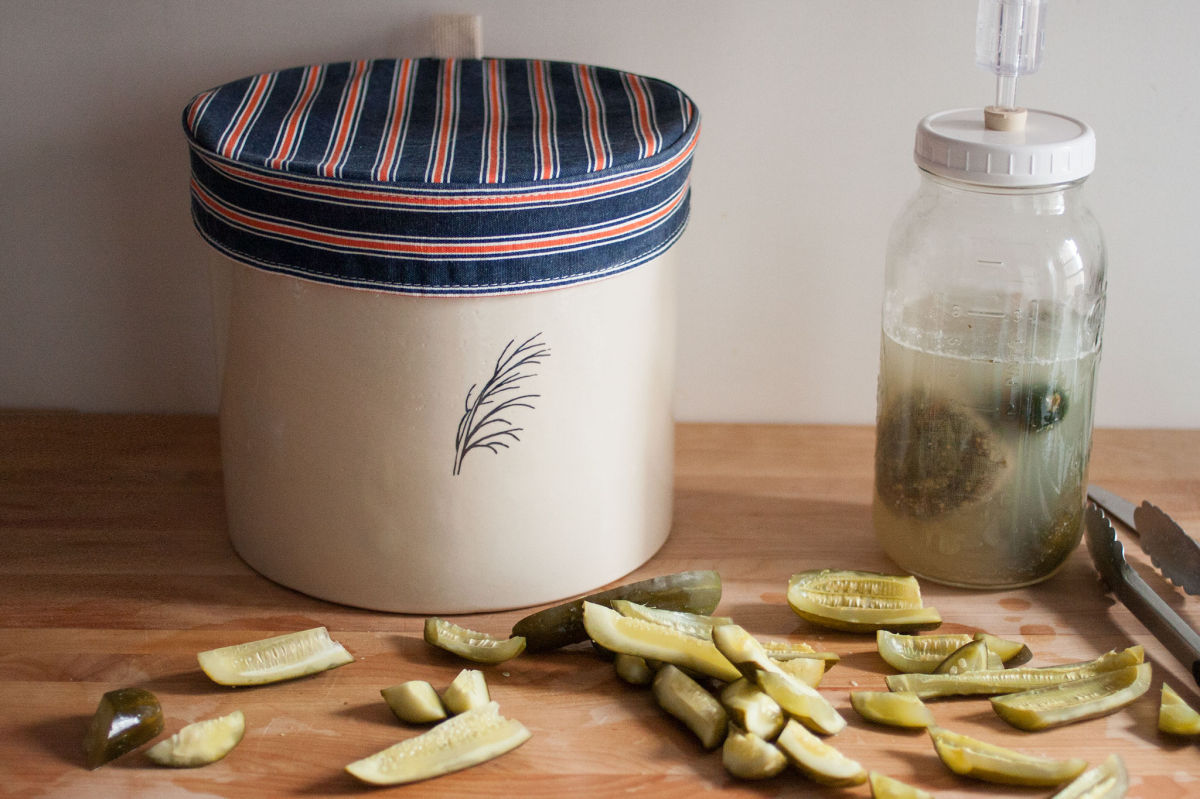 Pickles in front of a crock and a jar