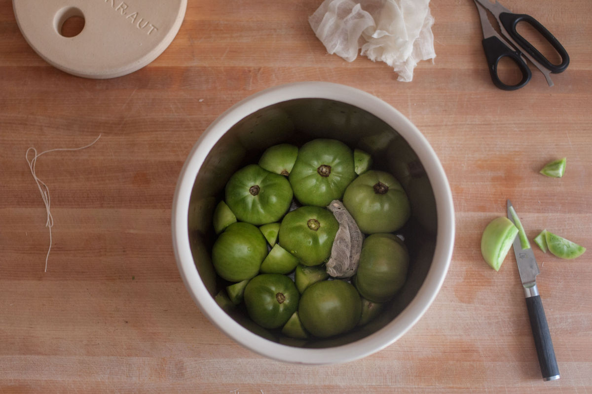 Making pickled green tomatoes in a fermentation crock
