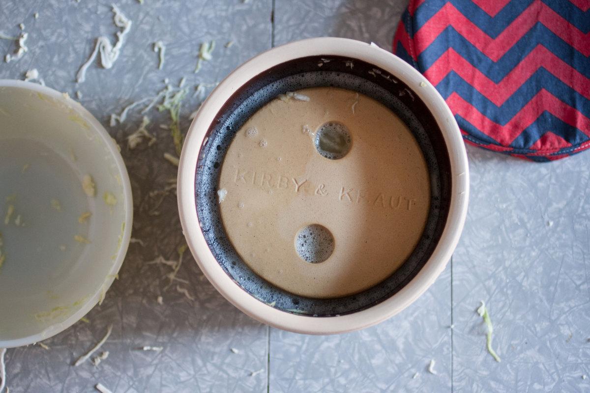 Sauerkraut held beneath the brine by a crock weight